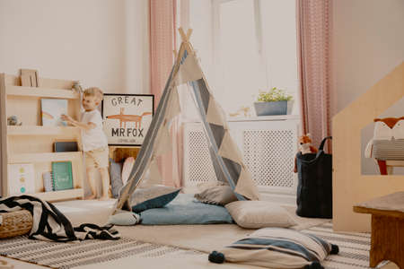 Scandinavian tent with pillows in the middle of stylish kids room in elegant apartment Stock Photo