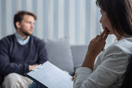 Thoughtful psychotherapist during session with sad patient with anxiety problem