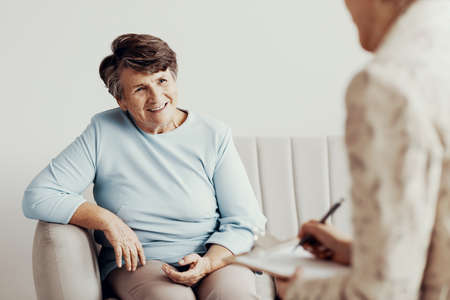 Smiling senior woman talking with financial advisor about life savings Stock Photo