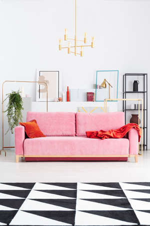 Gold lamp above pink couch in white apartment interior with patterned carpet and posters. Real photo