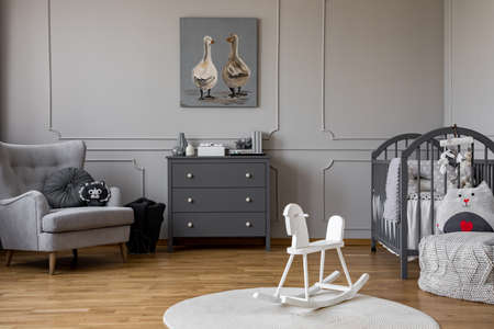 White rocking horse on rug in grey kids bedroom interior with poster above cabinet. Real photo