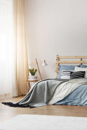 Light blue bedding, grey blanket and black and white pillows on double bed in elegant bedroom , real photo with copy space