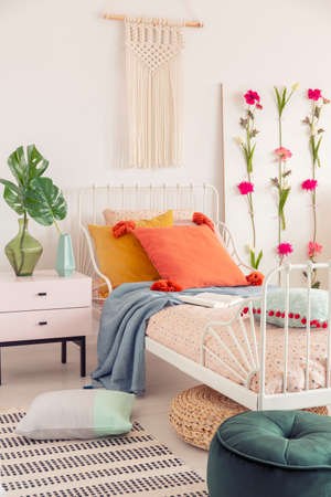 White handmade macrame above above single metal bed with colorful pillows and patterned duvet, real photo