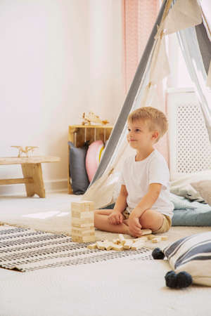 Vertical view of boy sitting in scandinavian kids playroom playing with wooden blocks, real photo with copy space on the white empty wall