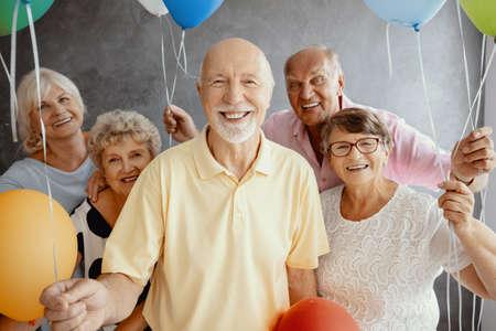 Ancianos sonrientes con globos divirtiéndose durante el cumpleaños de un amigo