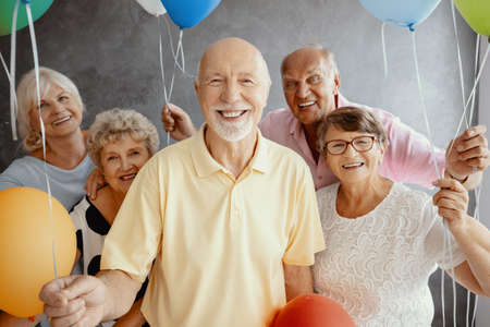 Smiling elderly people with balloons having fun during friend's birthday