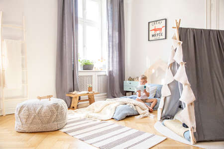 Cute boy sitting on bed in scandinavian bedroom interior with tent and big comfortable pouf, real photo