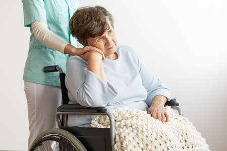 Nurse supporting sad disabled elderly woman in the wheelchair