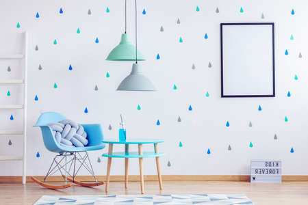 Mint green and grey lamps above blue wooden table in kid's room with white mockup poster on the wall