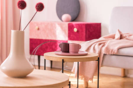 Round wooden table with cups on pink plate in living room interior with flowers in vase. Real photo 스톡 콘텐츠