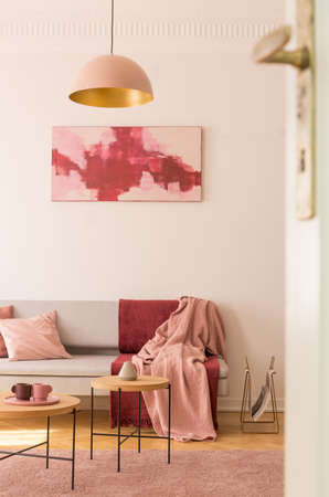 Lamp above wooden tables on pink carpet in loft interior with red poster above grey sofa. Real photo