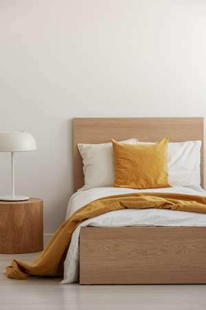 Yellow pillow and blanket on white bedding in simple hotel room with single bed, copy space on empty wall Stock Photo
