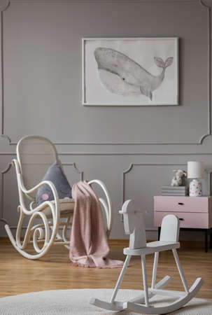 Rocking horse and armchair in grey kids room interior with poster and pink cabinet. Real photo Stock Photo