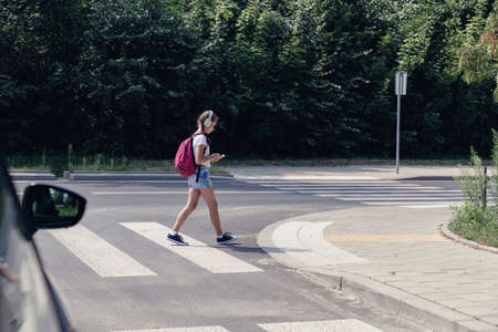 Young girl crossing a street while listening to music and looking at smartphone Banque d'images