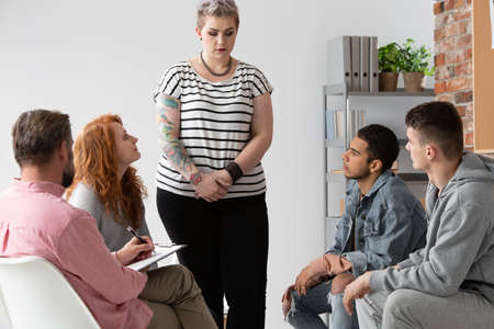 Tattooed girl with post traumatic disease standing in group of young people and their therapist during psychotherapy