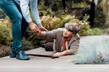 Uomo che aiuta una donna anziana a rialzarsi da terra