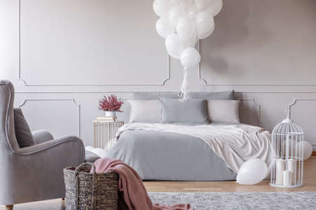 Bunch of white balloons above cozy double bed with grey bedding and white blanket, copy space on the empty wall and basket and armchair in the corner