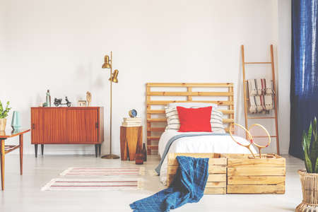 Real photo of a vintage bedroom interior with a cupboard, bed and wooden decorations