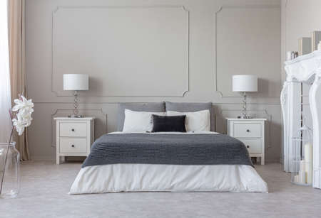 Grey blanket on white bedding on comfortable king size bed, two nightstand with lamps on both sides of it Stock Photo