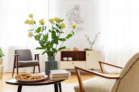 Armchair at table with flowers, books and food in bright apartment interior with windows. Real photo Standard-Bild
