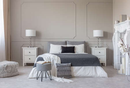 Grey pouf with open book in the food of king size bed with grey and white bedding, copy space on empty wall