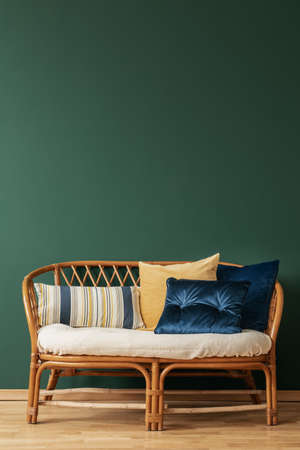 Rattan sofa with pillows in elegant living room interior with copy space on the empty green wall