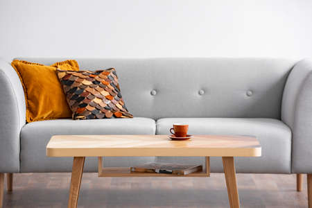 Wooden table with cup in front of grey sofa with pillows in simple living room interior. Real photo Stock Photo