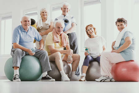 Group of active seniors sitting on exercising balls in modern fitness center after sports training