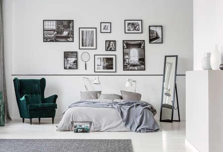 Cama gris entre sillón y espejo en interior de dormitorio con galería y lámparas. Foto real