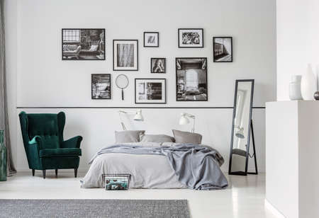 Grey bed between armchair and mirror in bedroom interior with gallery and lamps. Real photo