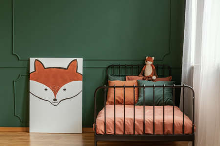 White poster with fox next to single metal bed with orange and dark green bedding Standard-Bild