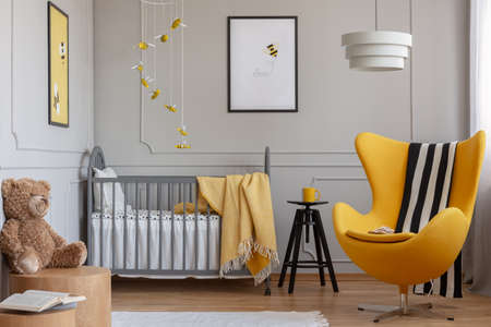 Black and white blanket on yellow armchair next to grey wooden crib with white bedding Stock Photo