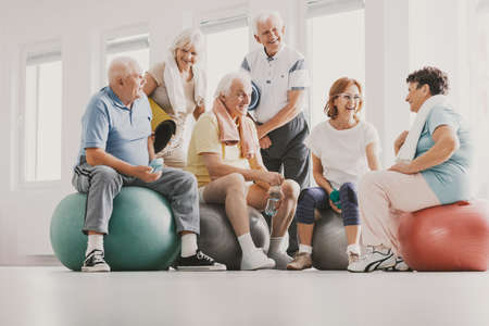 Group of happy senior sitting on exercising balls in bright fitness center before training