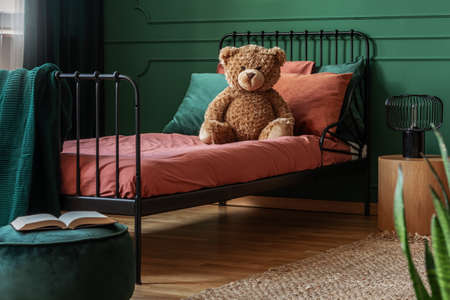 Brown teddy bear on single metal bed with burn orange and emerald green bedding