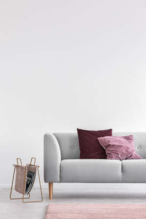 Pillows on grey couch and pink carpet in white living room interior with copy space. Real photo