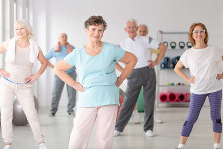 Group of happy seniors during sports training at gym