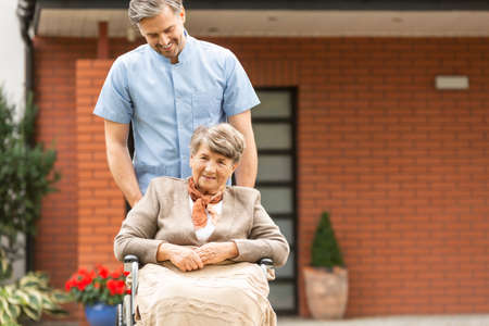 Senior in a wheelchair and male nurse in a garden