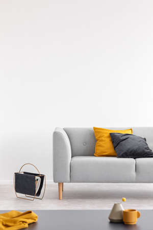 Yellow and black cushion on grey sofa in white loft interior with table and copy space. Real photo Stock Photo