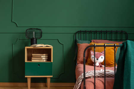 Plush toy and pillows on single metal bed next to wooden nightstand with books and industrial lamp
