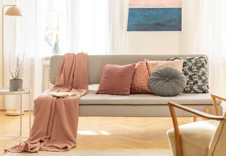 Colorful pillows and blanket on comfortable grey couch Standard-Bild