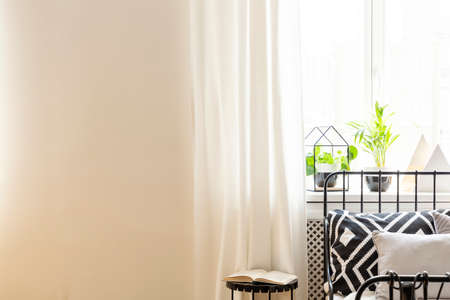 Table next to bed with patterned cushion in white bedroom interior with copy space. Real photo