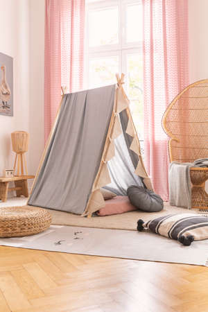 Grey tent and rattan chair in a kid room interior. Real photo