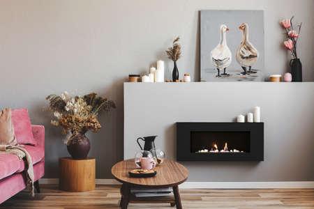 Elegant woonkamerinterieur met zwarte en grijze open haard, houten salontafel en roze bank