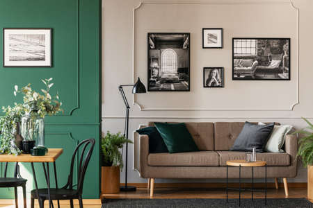 Black and white photos on grey wall of chic living and dining room interior with brown couch and wooden table