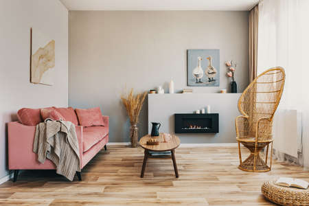 Wicker peacock chair, wooden coffee table and pink couch in grey living room interior
