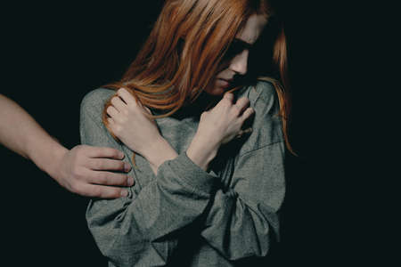 Strangers hand put on scared young redhead womans arm as a symbol of abuse 스톡 콘텐츠