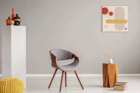Trendy grey and wooden chair in retro living room interior Reklamní fotografie