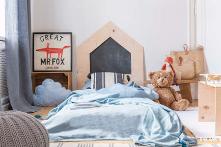 Graphic, bed with blue sheets and a teddy bear in a boy bedroom interior. Real photo