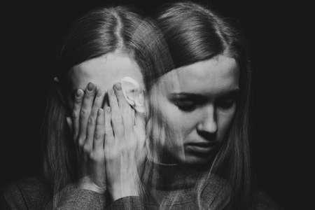 Schwarz-weißer Träger eines schönen rothaarigen Mädchens mit psychotischen Störungen, das ihr Gesicht bedeckt und sich vor ihren Halluzinationen versteckt Standard-Bild