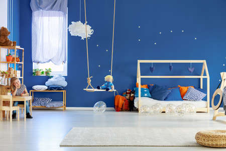 Cute blond girl sitting at wooden table in stylish baby room with Blue wall with golden stars and scandinavian wooden house shape bed with pillows Stok Fotoğraf